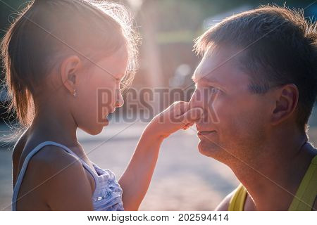 Cute little girl and her handsome father are talking and smiling. Daughter is touching his dad's nose.