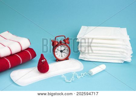 Medical conceptual photo. Red dreamy smile crochet blood drop daily and menstrual pad and tampon. Woman critical days gynecological menstruation cycle. Menstruation sanitary woman hygiene