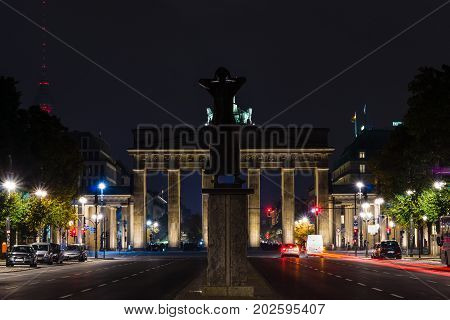 BERLIN GERMANY - OCTOBER 13 2015: A view of the Brandenburg Gate from the 17th of June Street. In the foreground a sculpture Der Rufer (The Caller)
