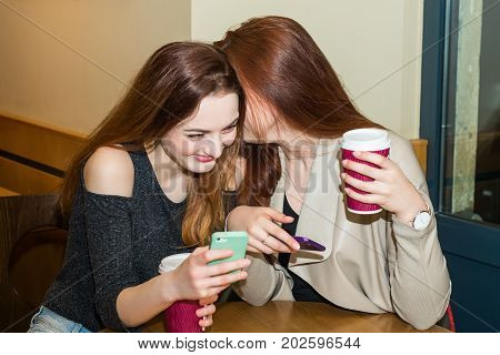 Two beautiful women drinking coffee mug, gossiping and chatting in a cafe bar. Two girls sitting in a cafeteria, gossiping and laughing