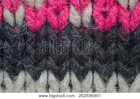 Texture of a beige knitted sweater close-up. Three-color abstract pattern knitted winter sweater