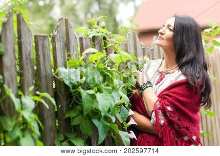 Beautiful adult village woman in a shawl near a wooden fence