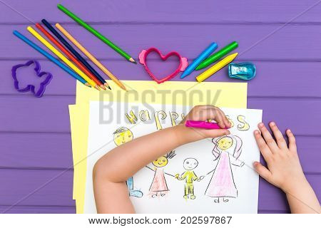 The top view of the child paints a sketch of the family with colored pencils on a white sheet of paper. The word happyness is written on the sheet