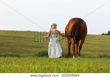 Blonde woman in summer dress walk slowly through meadow beside her horse