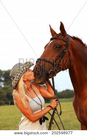 Portrait of woman and her horse on summer afternoon