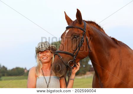Smilling woman and horse in summer afternoon