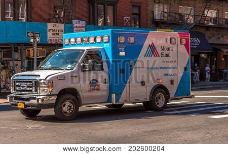 New York NY USA August 3 2016 -- A red white and blue hospital ambulance threads its way along a Manhattan street. Editorial Use Only.