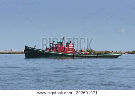 Cleveland, USA - August 26, 2017: Built in 1915, the 102 year old Great Lakes tugboat Iowa continues to assist freighters arriving on Lake Erie navigate the Cuyahoga River and the Port of Cleveland to this day