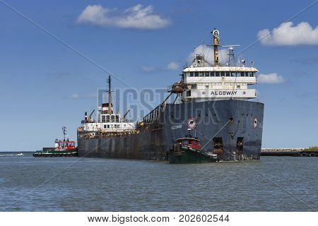 Cleveland, USA - August 26, 2017: The 45 year old Great Lakes bulk carrier Algoway, rumored to be scheduled for scrapping, is entering the Cuyahoga River assisted by the tugboats Iowa and Cleveland