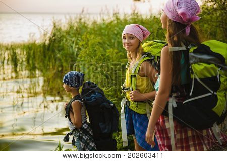 Teenager travelers with backpacks standing on coast. Wanderlust travel concept.
