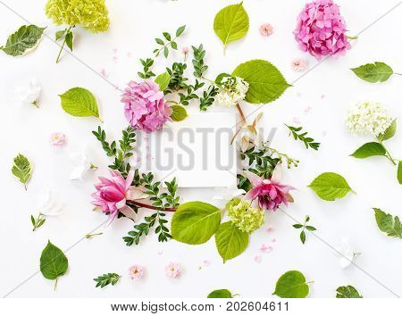 White Fabric Mock-up With Blooming Flowers, Leaves And Petals Around It. Flat Lay, Top View
