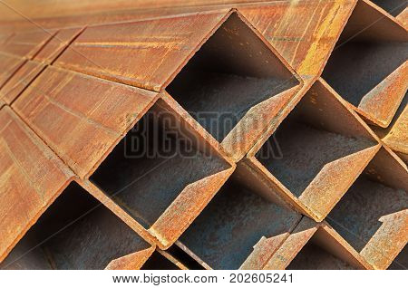 The manufactured by welding rusty square steel pipes piled up warehouse outdoor