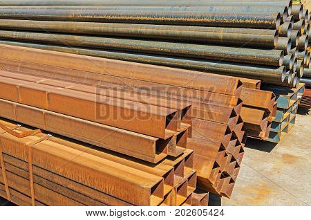 The manufactured by welding square and round rusty steel pipes piled up warehouse outdoor