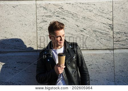 Portrait of attractive hipster guy in stylish black leather jacket over white t-shirt relaxing outdoors on sunny spring day enjoying takeaway hot cappuccino or herbal tea out of disposable papercup