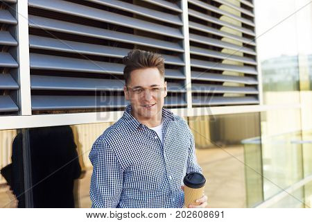 People urban lifesyle and relaxation concept. Attractive happy young Caucasian man holding disposable papercup drinking coffee-to-go on street looking at camera with joyful expression on his face