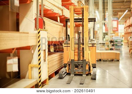 Forklift loader standing near shelves with wooden boards in storehouse