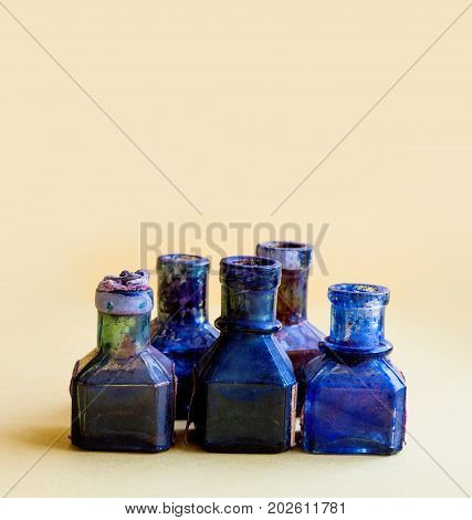Vintage bottles close-up. Colorful dirty blue glasses on yellow background, shallow depth of field. copy space