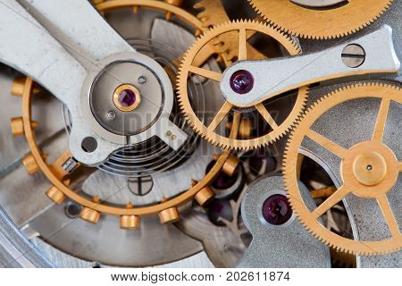 Stopwatch chronometer mechanism cogs gears wheels connection concept. Clock transmission macro view. Shallow depth of field, selective focus