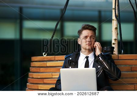 Always in touch. Picture of attractive young Caucasian male entrepreneur sitting on bench with laptop pc using free wi-fi for remote work checking e-mail and talking on mobile phone simultaneously