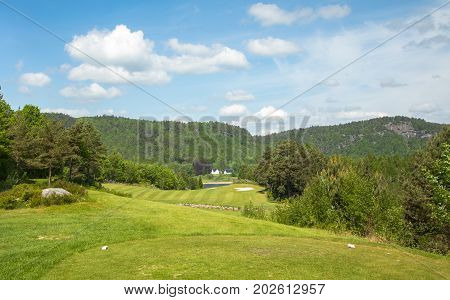 Landscape on Bjaavann golf course with green grass, trees, beautiful blue sky and a sand trap in the background, panorama