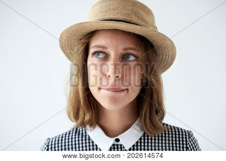 Headshot of doubtful thoughtful young female looking up and curving her lips trying to make decision. Indecisive blue-eyed woman in round hat thinking something over. Human facial expressions