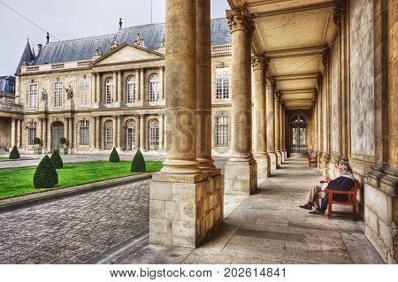 France, Paris - March 2008: Elderly man reading a book in musee des Archives nationales (Musee de l'Histoire de France), hotel de Soubise. Paris. France