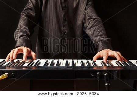 Musician playing the electronic piano on a black background