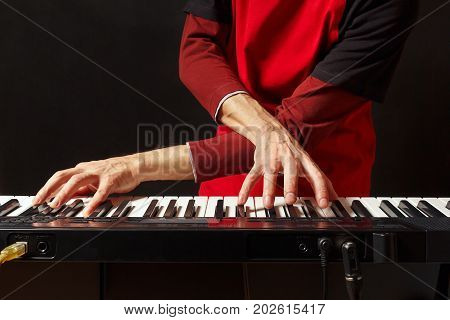 Musician play the keys of the electronic piano on a black background