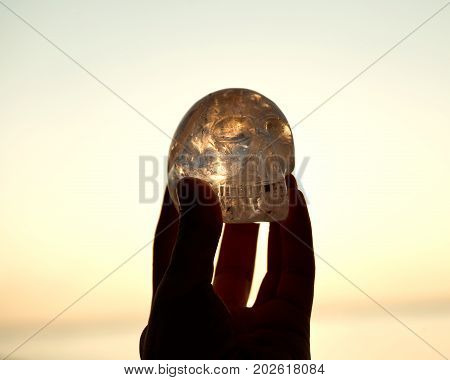 Woman`s hand holding clear quartz skull in front of the rising sun