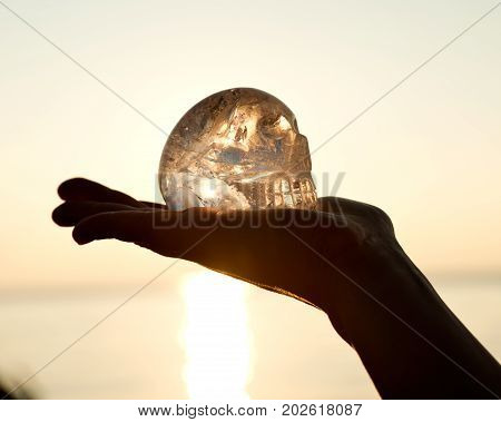 Clear quartz skull on the woman`s open palm in front of  the rising sun