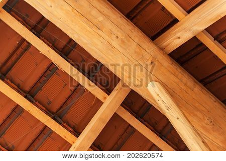 Wooden beams under a red brick roof during. Detail of wooden roof structure