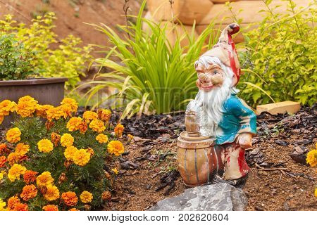 An old broken dwarf in the garden. Decoration in flowerbed