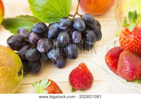 Fresh fruits. Healthy food. Mixed fruits are grapes, pears, peaches, strawberries. eat, diet, like fruit. Studio photography of various fruits on an old wooden table. Organic healthy assorted fruits. Assortment of fresh fruits. . Fruit food background. He