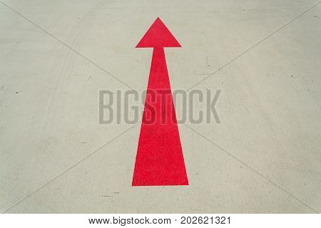 Red Arrow Direction Sign On Gray Concrete Road Sunny Day