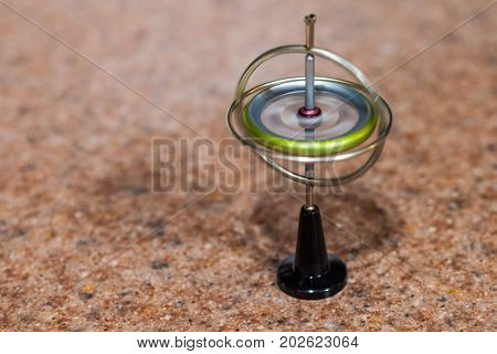 Toy gyroscope spinning and balancing on a small stand