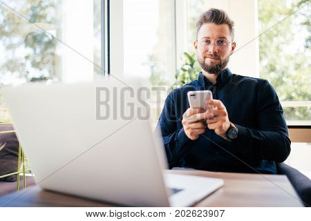 Young Happy Businessman Smiling Sitting In Office With Laptop While Reading His Smartphone. Portrait