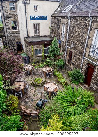 STIRLING, SCOTLAND: JULY 23: Exterior walls and courtyard of the landmark Portcullis  Hotel on July 23, 2017 at Stirling, Scotland. The hotel is immediately outside the gates of Stirling Castle.