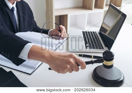 Close up of Male lawyer or judge hand's striking the gavel on sounding block working with Law book report the case on table in modern office Law and justice concept.