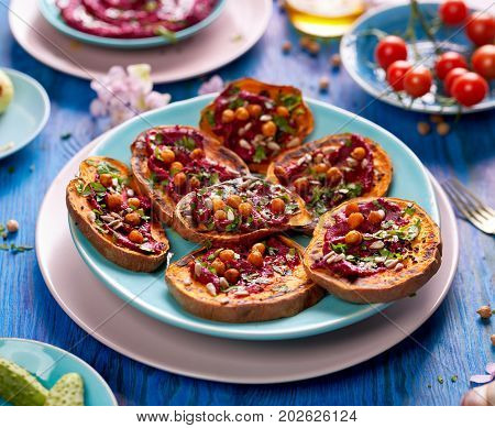 Sweet potato toast with beet hummus, grilled chickpeas, fresh parsley, nigella seeds  and sunflower seeds on a plate on a blue table. A nutritious and delicious vegan meal
