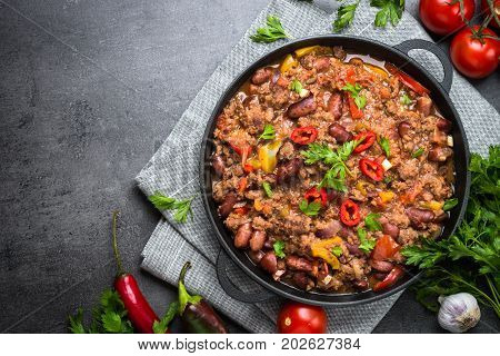 Chili con carne in a cast iron pan on black slate table. Traditional mexican fod. Top view copy space.