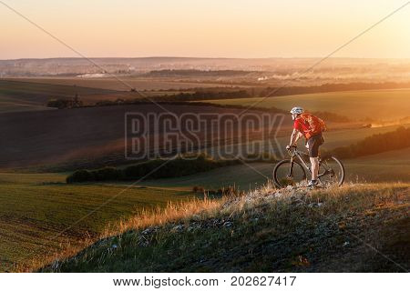 Traveler in red jersey and white helmet ride a bike on autumn background