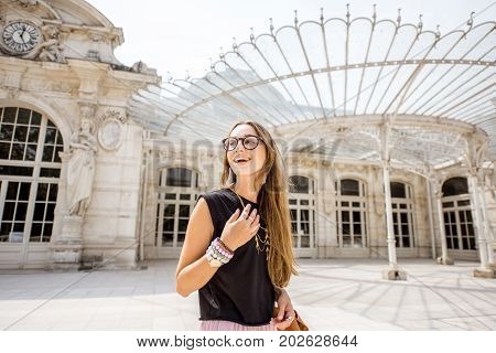 Lifestyle portrait of a woman walking near the beautiful old opera building in Vichy city in France