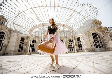 Lifestyle portrait of a woman in skirt spining near the beautiful old opera building in Vichy city in France