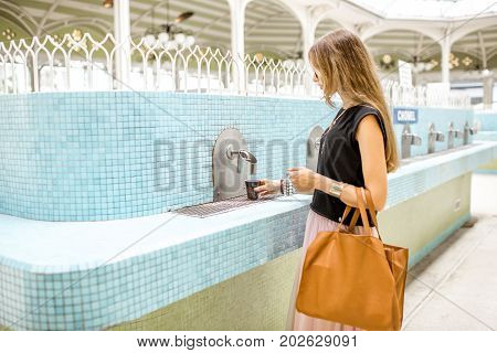 Young woman pouring thermal healing water into the plastic cup in the pump room in Vichy city, France