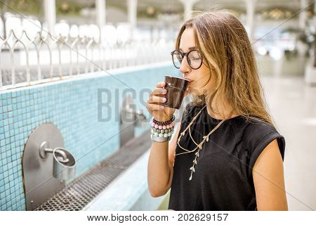 Young woman drinking thermal healing water in the old pump room in Vichy, France
