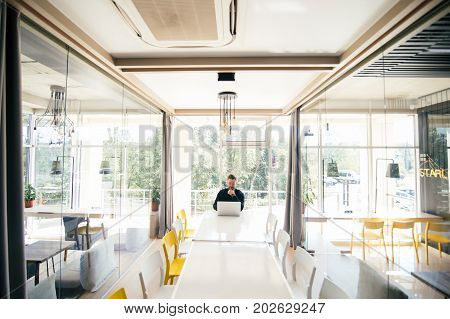 Bearded Handsome Businessman Sitting At The Big Conference Romm White Table And Working At Laptop Be