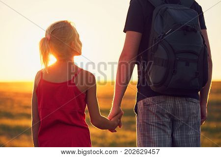 Summertime trip in the countryside. Girl holding hand his father at the sunset. - back lit