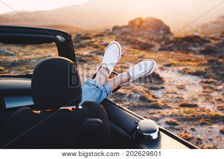 Happy Woman Traveler Rests And Admire Sunset In Mountains From Convertible Car. Woman Pushes Her Sho
