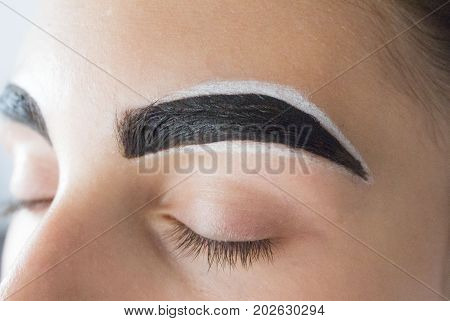Eyebrow architecture. Eyebrow shaping. Correction makeup and color to the eyebrows with henna in a beauty salon.