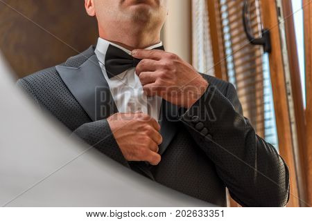 Male hands correct wedding bowtie on white shirt